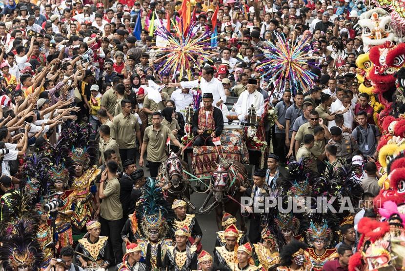Capres dan Cawapres Nomor Urut 01, Joko Widodo dan Maruf Amin (tengah) menyapa masyarakat saat kampanye Karnaval Indonesia Satu di Tangerang, Banten, Ahad (7/4/2019).