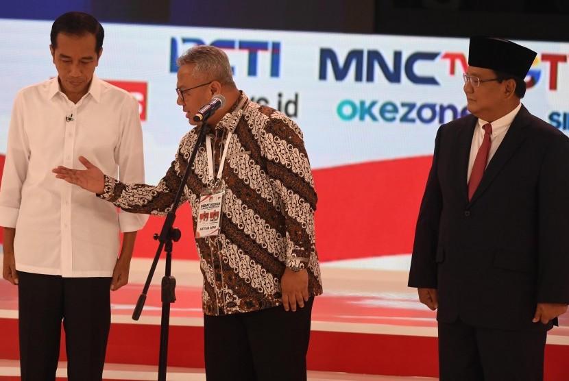Capres nomor urut 01 Joko Widodo (kiri) dan Capres nomor urut 02 Prabowo Subianto (kanan) bersiap memulai debat capres 2019 disaksikan Ketua KPU Arief Budiman (tengah) di Hotel Sultan, Jakarta, Ahad (17/2/2019).