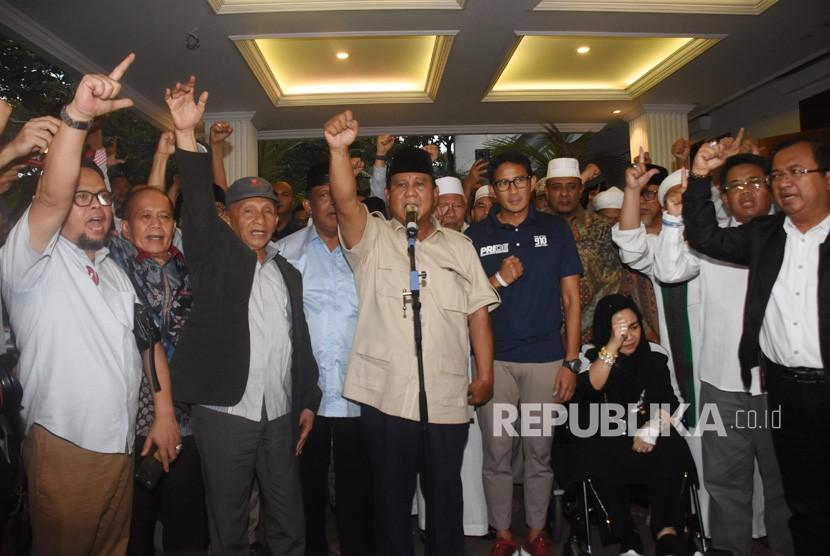 Capres nomor urut 02 Prabowo Subianto (tengah) bersama Cawapres Sandiaga Uno dan petinggi partai pendukung mengangkat tangan saat mendeklarasikan kemenangannya pada Pilpres 2019 kepada awak media di kediaman Kertanegara, Jakarta, Kamis (18/4/2019).
