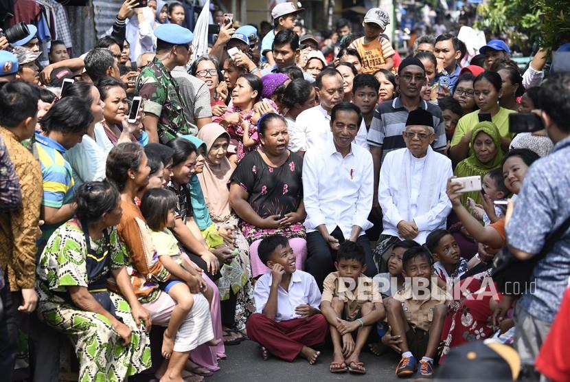 Capres petahana Joko Widodo dan cawapres Ma'ruf Amin menyapa warga usai menyampaikan pidato kemenangannya sebagai Presiden Republik Indonesia periode 2019-2024 di Kampung Deret, Tanah Tinggi, Johar Baru, Jakarta Pusat, Selasa (21/5/2019).