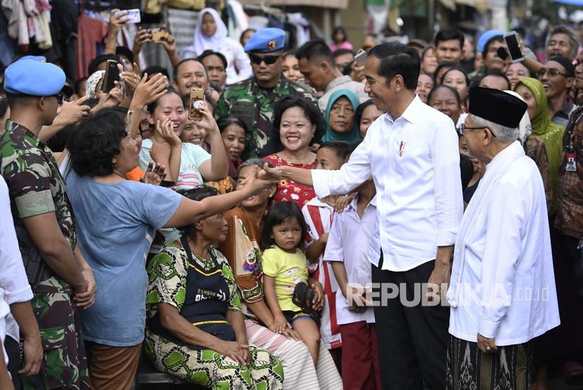 Capres petahana Joko Widodo (kedua kanan) dan cawapres Ma'ruf Amin (kanan) menyapa warga usai menyampaikan pidato kemenangannya sebagai Presiden Republik Indonesia periode 2019-2024 di Kampung Deret, Tanah Tinggi, Johar Baru, Jakarta Pusat, Selasa (21/5/2019).