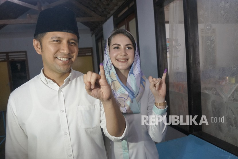 Cawagub Jatim Emil Elestianto Dardak (kiri) didampingi istri, Arumi Bachsin, menunjukkan bekas tinta pada ujung jari kelingking tanda telah menyalurkan hak pilih (mencoblos) di TPS 05 Kelurahan Ngantru, Trenggalek, Jawa Timur, Rabu (27/6).