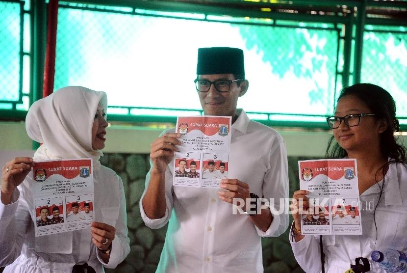 Cawagub Sandiaga Uno bersama keluarga menunjukkan surat suara saat akan pencoblosan di TPS 01 kawasan Senayan, Jakarta, Rabu (19/4).