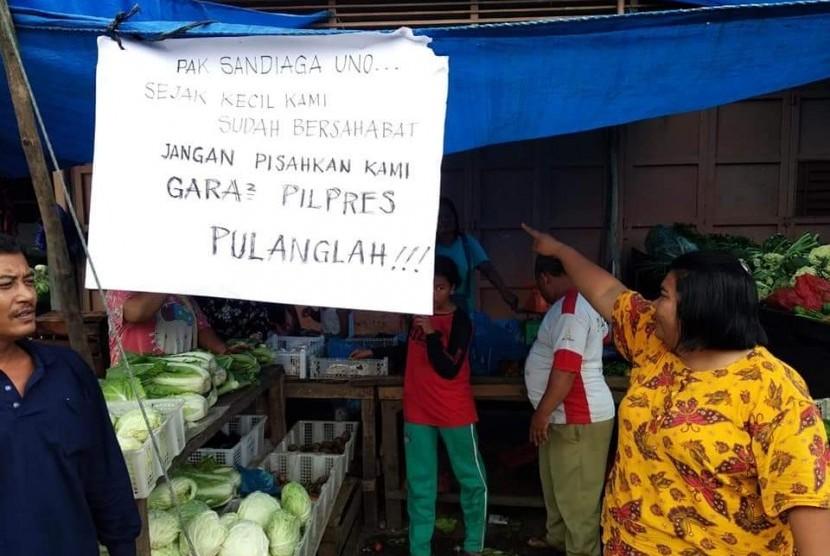 Cawapres nomor urut 02 Sandiaga Salahuddin Uno disambut poster bertuliskan imbauan larangan hadir di Pasar Kota Pinang, Sumatera Utara, Selasa (11/12).