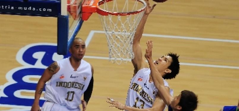 Center tim basket Indonesia, Rony Gunawan, berusaha melakukan lay up melewati hadangan pebasket Malaysia dalam laga kejuaraan South East Asia Basketball Association (SEABA) 2011, di Britama Arena Sportmall, Jakarta, Sabtu (25/6).
