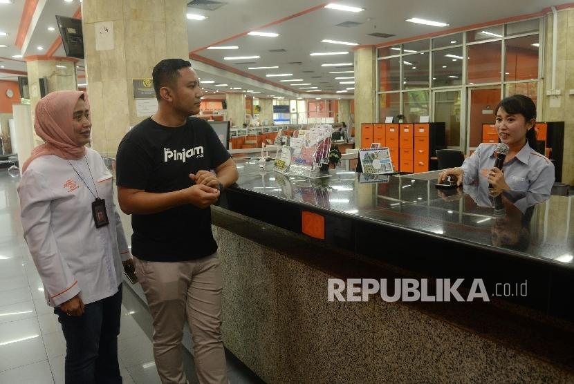 Co-Founder dan Chief Executive Officer Pinjam.co.id Teguh Ariwibowo (kedua kanan), bersama Direktur Ritel dan SDM PT Pos Indonesia Ira Puspadewi (kiri) mendengarkan penjelasan dari karyawan tentang layanan gadai antara Pinjam.co.id dengan PT Pos Indonesia di kantor Pos Pusat, Jakarta, Rabu (25/10).