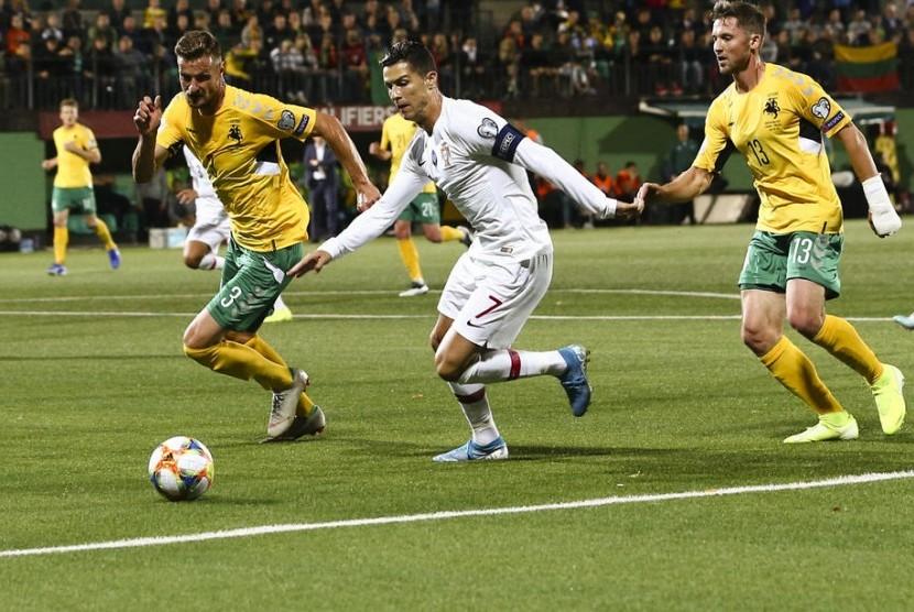 Cristiano Ronaldo (tengah) menggiring bola saat membela Portugal melawan Lithuania.
