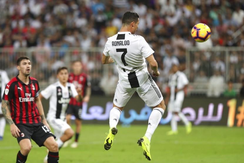Crsitiano Ronaldo (kanan) saat hendak menanduk bola untuk menjebol gawang AC Milan pada laga Piala Super Italia.