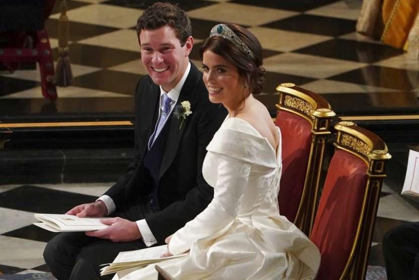 Cucu Ratu Elizabeth, Putri Eugenie dari York dan Jack Brooksbank tersenyum saat pernikahan mereka di St George's Chapel, Istana Windsor, Inggris, Jumat (12/10).