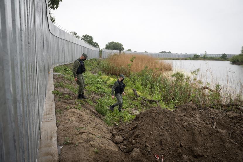 Dalam foto arsip 21 Mei 2021 ini, polisi berpatroli di sepanjang dinding baja di sungai Evros, dekat desa Poros, di perbatasan Yunani-Turki, Yunani. Dihantui oleh krisis migrasi 2015 yang dipicu oleh perang Suriah, para pemimpin Eropa sangat ingin menghindari masuknya migran dan pengungsi skala besar lainnya dari Afghanistan.