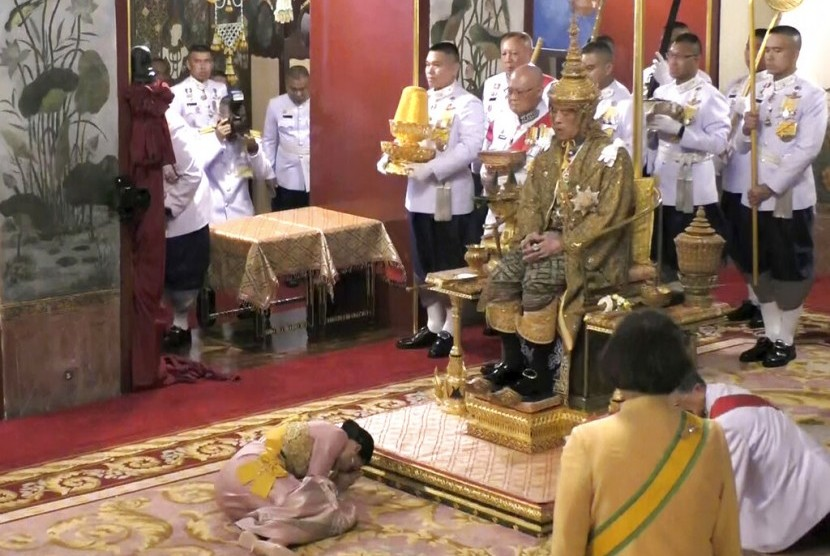 Dalam foto tangkapan video, Raja Thailand Maha Vajiralongkorn duduk di singgasana di depan Ratu Suthida saat secara resmi dinyatakan sebagai raja di Grand Palace, Bangkok, Sabtu (4/5).