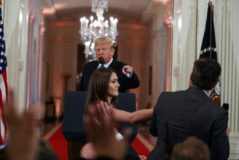 Dalam foto yang diambil pada 7 November 2018 ini, Presiden AS Donald Trump menyaksikan seorang pembantu Gedung Putih mengambil mikrofon dari wartawan CNN Jim Acosta saat konferensi pers. CNN menuntut Trump untuk membuka kembali akses Acosta ke Gedung Putih.