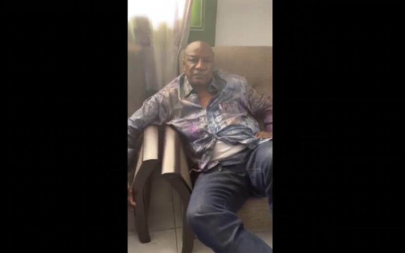 Dalam gambar yang diambil dari video pada hari Minggu, 5 September 2021, Presiden Guinea Alpha Conde duduk di sofa di lokasi yang tidak diketahui.