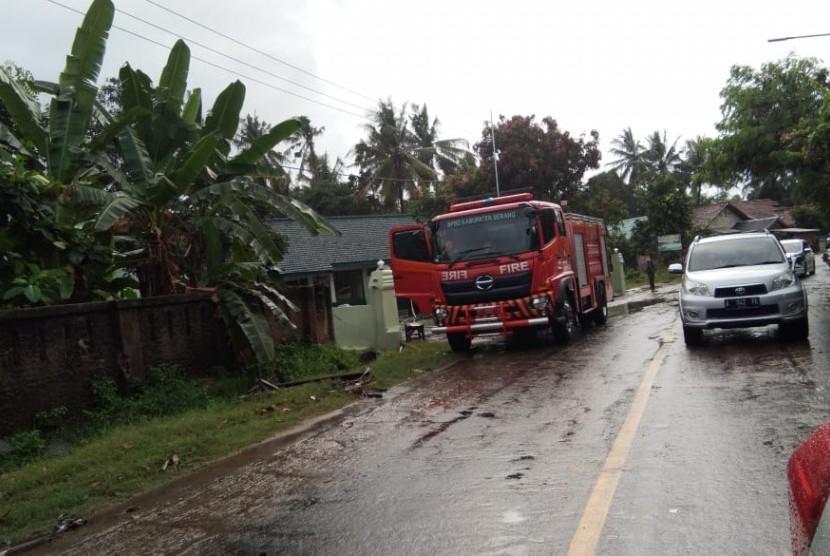 Damkar membersihkan Jalan Raya Anyer yang semalam berantakan tersapu tsunami, Ahad (23/12).