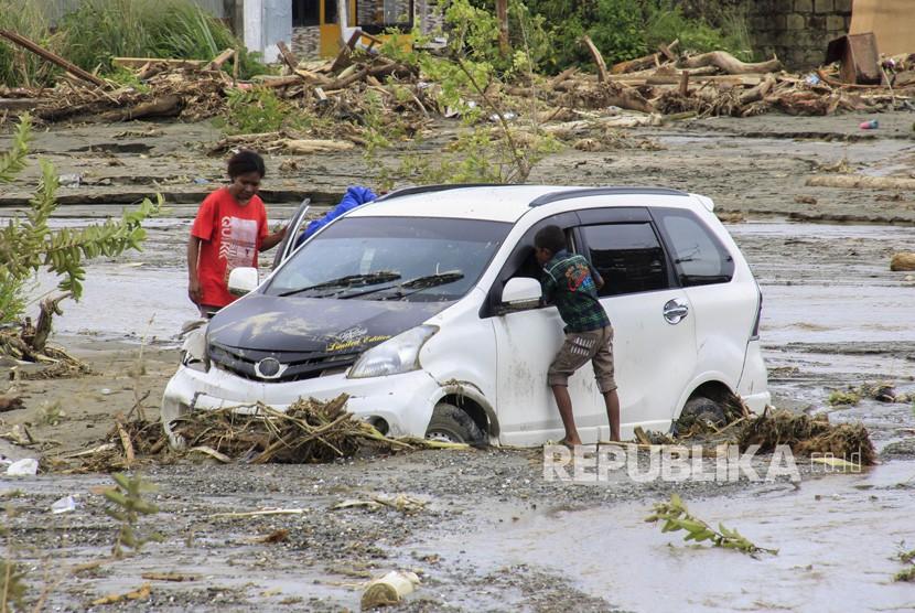 Dampak Banjir Bandang Sentani. Kendaraan terendam lumpur saat banjir bandang di Sentani, Kabupaten Jayapura, Papua, Ahad (17/3/2019).