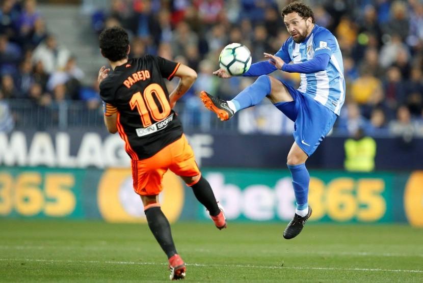 Daniel Parejo berebut bola dengan pemain Malaga Manuel Ittura (kanan).