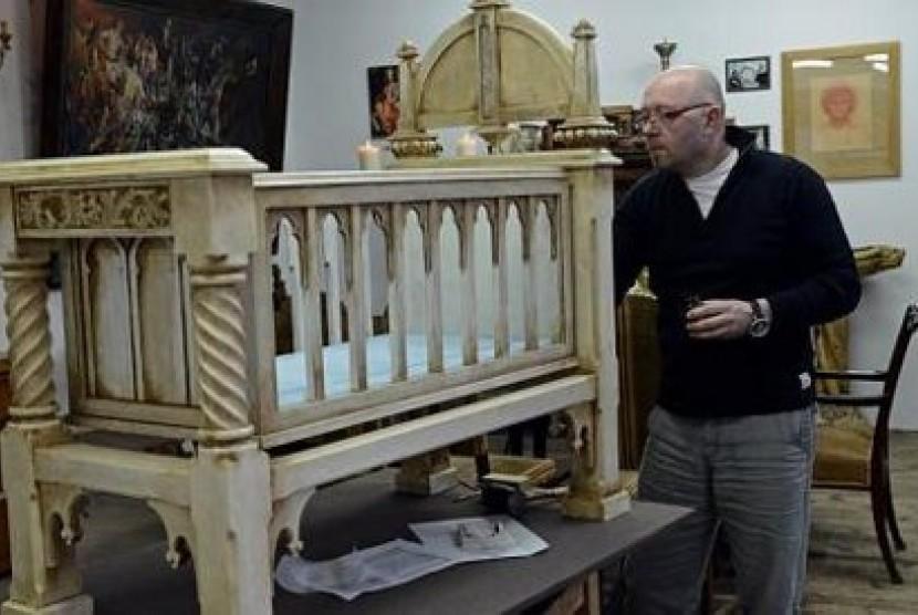 Dariusz Bergier, seniman pahat, pembuat perabot dan pakar restorasi sedang menggarap tampat tidur bayi gaya Gothic untuk bayi pertama Pangeran William dan Kate Middleton.