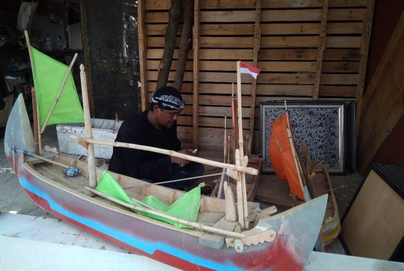 Darmin (37 tahun) seorang perajin miniatur perahu mainan tradisional di Rumah Berdikari, Desa Karangsong, Kabupaten Indramayu, sedang membuat perahu mainannya.
