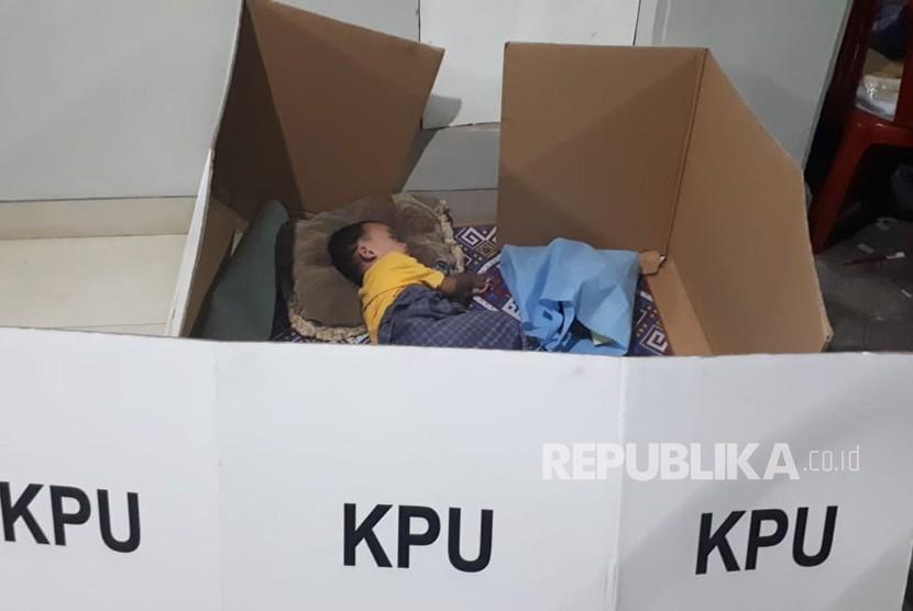 Demi menjaga TPS pada malam hari, seorang ibu yang juga anggota KPPS di TPS  01 membawa anaknya nginep di TPS. Sang ibu menjaga TPS dimalam hari, sang  anak istirahat.