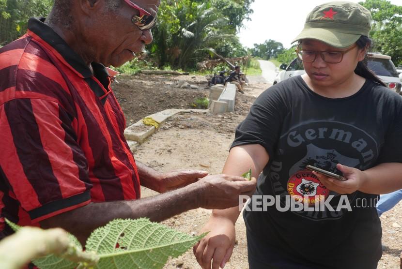 Wellem Kalami sedang meniup un untuk memgumpulkan warga, berlatar belakang Pulau Um. Warga berkumpul untuk membangun, tetapi tidak jika harus membabat hutan.