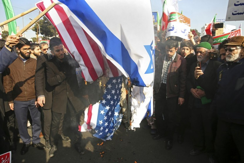 Demonstran Iran membakar bendera AS dan Israel di Mashhad, Iran, Kamis (4/1).