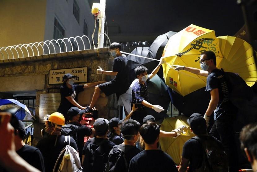 Demonstran menggunakan payung dan cat semprot saat mengepung markas polisi di Hong Kong, Kamis dini hari (27/6).
