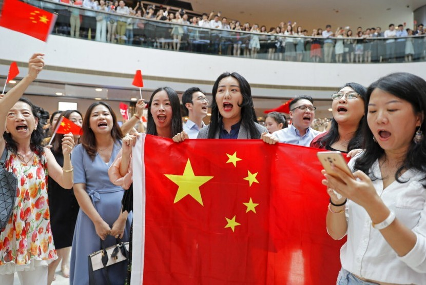 Demonstran pro-China memegang bendera dan menyanyikan lagu nasional di pusat perbelanjaan International Finance Centre (IFC) di Hong Kong, Kamis (12/9). Ribuan demonstran prodemokrasi bernyanyi di pusat perbelanjaan.