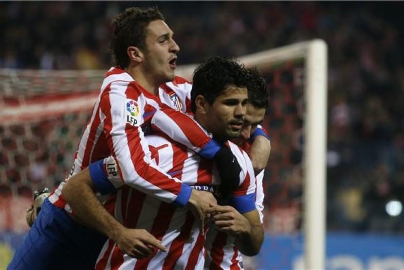 Diego Costa (tengah), pemain Atletico Madrid, merayakan golnya bersama rekan setim saat menghadapi Sevilla di leg pertama babak semifinal Piala Raja Spanyol di Vicente Calderon, Madrid, Kamis (31/1).