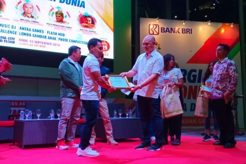 Direktur Anak Bangsa Juara Michael Umbas menyerahkan penghargaan kepada atlet Indonesia yang berprestasi di Asian Games.