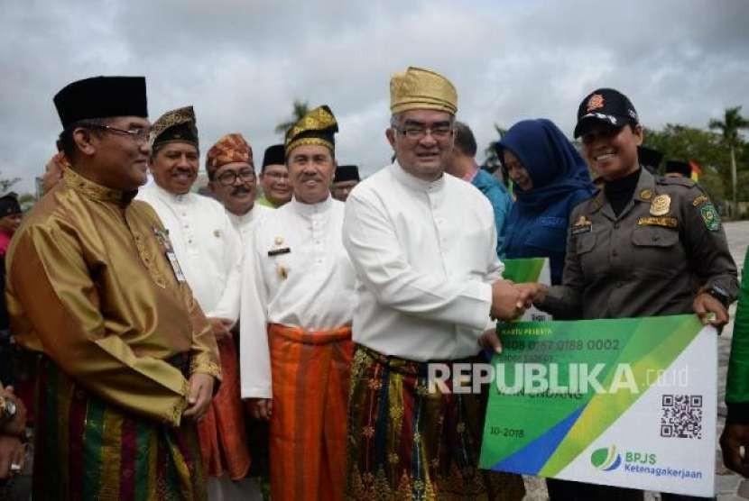 Direktur Investasi BPJS Ketenagakerjaan Amran Nasution menyerahkan katru kepada para perwakilan pekerja rentan penerima BPJS ketenagakerjaan disaksikan Bupati Siak Syamsuar (tengah) dan Direktur Utama Bank Riau Kepri Irvandi Gustari (kiri) di kantor Bupati Siak, Riau, Jumat (12/10)