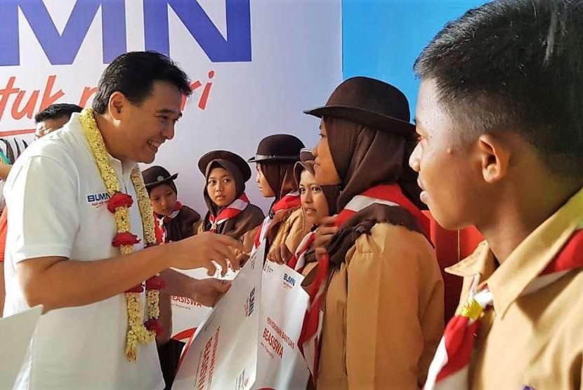 Direktur Keuangan Telkom Harry M. Zen saat menyerahkan bantuan beasiswa kepada pelajar SD Al Rahmah Cilincing, Jakarta Utara (18/8).