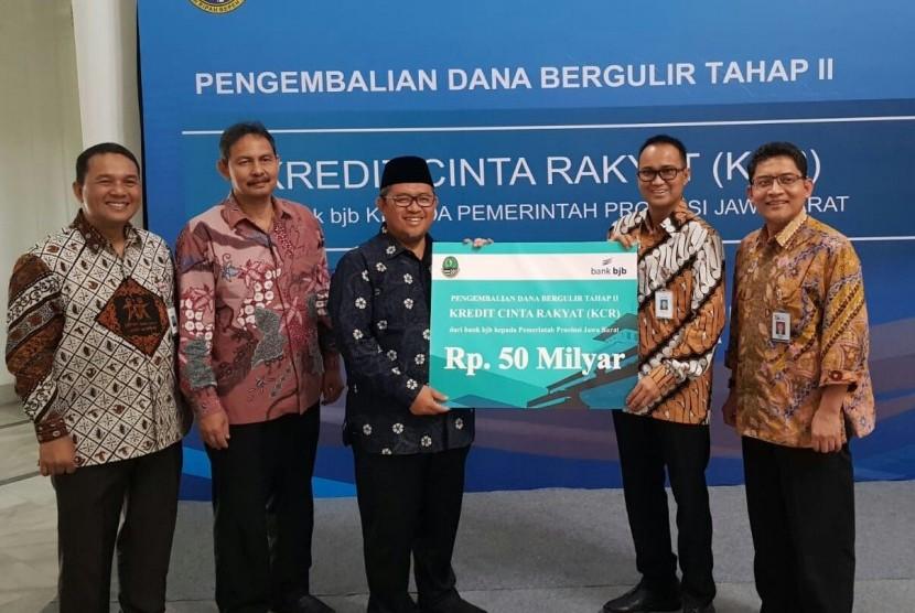 Direktur Komersial dan UMKM Bank BJB Agus Gunawan (kedua dari kanan) menyerahkan secara simbolik pengembalian dana KCR kepada Gubernur Jabar Ahmad Heryawan di Gedung Sate, Kota Bandung, Jumat (8/6).