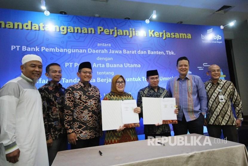 Direktur Konsumer Bank Bjb Suartini dan Dirut PT Praba Arta Buana Utama Afipuddien, memperlihatkan Perjanjian Kerjasama tentang Pemanfaatan Tandamata Berjangka Untuk Tujuan Umroh, di gedung Bank BJB, Jalan Naripan, Kota Bandung, Senin (15/4).