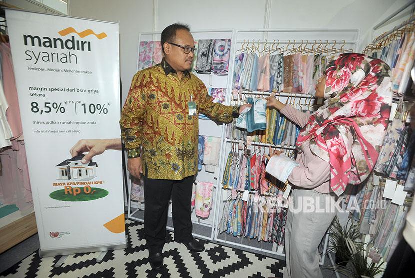 Direktur Mandiri Syariah Achmad Syafii (kiri) mendapat penjelasan dari penjaga stan nasabah UKM Mandiri Syariah usai membuka pameran Halal Life Style Mandiri Syariah yang berlangsung 4-6 Juni 2018, di Jakarta, Senin (4/6).