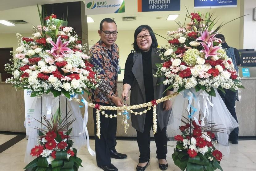 Direktur Omni Hospitals Pulomas, Hanny Merliana dan Kepala Bidang Pelayanan BPJSTK Cabang Rawamangun, Jakarta Timur, Tri Pambudi Santoso menggunting pita tanda kerja sama keduanya dimulai