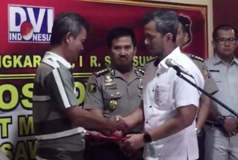 Direktur Operasional Lion Air, Wisnu (kanan) menyerahkan dokumen jenazah yang berhasil di identifikasi kepada keluarga, Kamis (31/10).