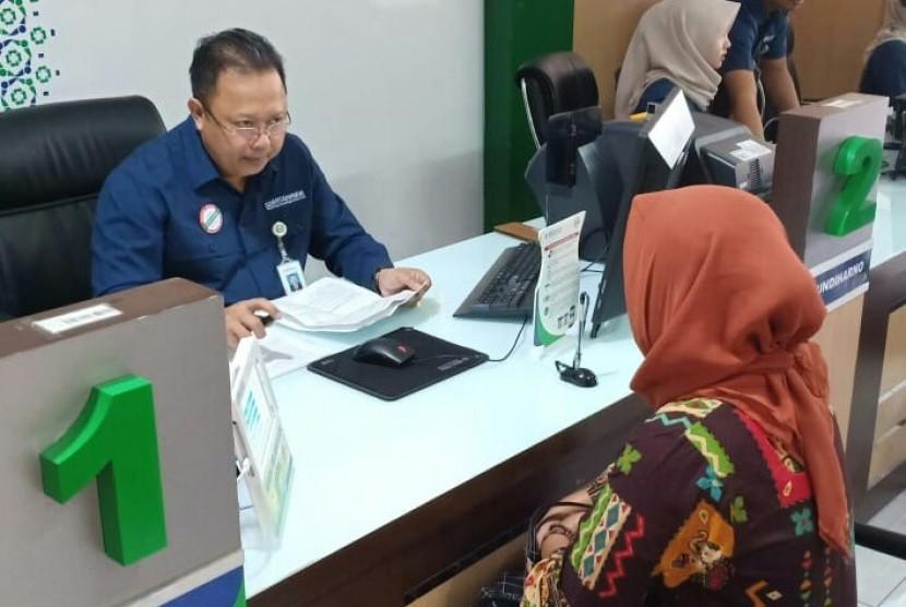 Direktur Perencanaan Pengembangan dan Manajemen Risiko BPJS Kesehatan Mundiharno mengambil alih sejenak peran frontliner di Kantor BPJS Kesehatan Cimahi, Kamis (12/7).
