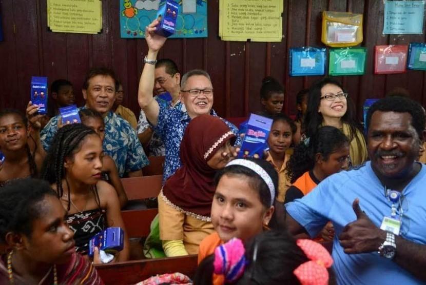 Direktur PT Bank Central Asia Tbk (BCA) Rudy Susanto (tengah) didampingi Executive Vice President CSR BCA Inge Setiawati (kiri) dan Senior Vice President CSR BCA Sapto Rachmadi (kanan) mengangkat kaleng tabungan bersama guru dan siswa siswi SD Negeri Inpres 26 Klamono, Sorong, Papua Barat, Jumat (21/4).