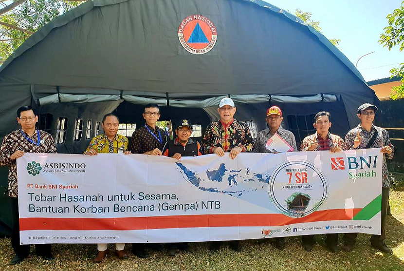 Direktur Utama BNI Syariah, Abdullah Firman Wibowo (keempat dari kanan) dan Bupati Lombok Utara, Najmul Akhyar (keempat dari kiri) mengunjungi pengungsi gempa di Lombok. Dalam kunjungan ini, BNI Syariah bersama Yayasan Hasanah Titik (YHT) memberikan bantuan berupa pembangunan rumah bagi warga, sembako, obat-obatan dan program trauma healing bagi anak - anak di Lombok (7/8).