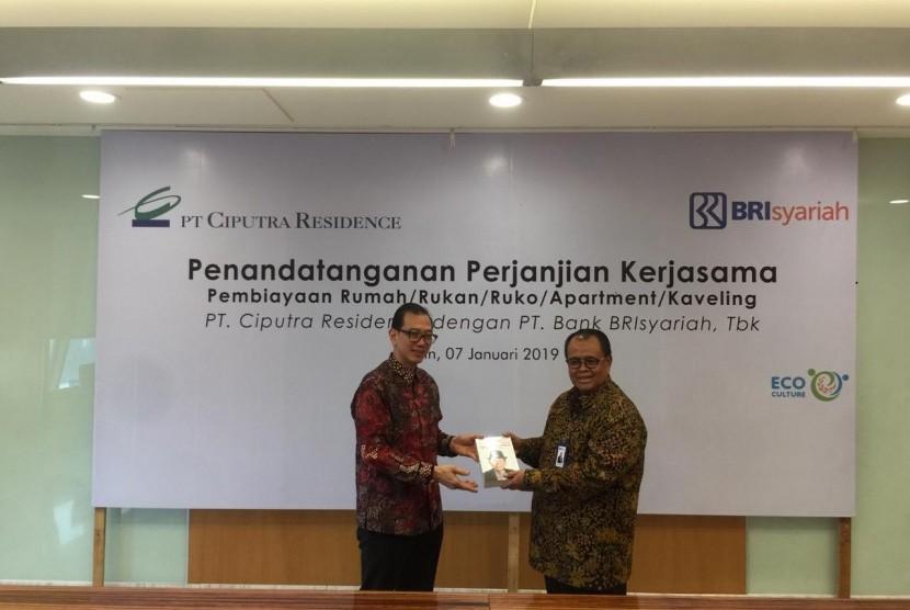 Direktur Utama BRIsyariah Moch. Hadi Santoso (kanan) usai menandatangani Perjanjian Kerjasama dengan Ciputra Group yang diwakili Marius Ignatius Meiko Handoyo Lukmantara (kiri) yang merupakan direktur di bawah Ciputra Group Holding 1.