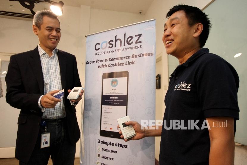 Direktur Utama Mandiri Capital Indonesia (MCI) Eddi Danusaputro (kiri), bersama CEO dan Co-Founder Chashlez Teddy Setiawan (kanan) menunjukkan produk MPOS (Mobile Point of Sale) yang ditawarkan Cashlez di sela memberikan keterangan pers kepada media di Jakarta, Rabu (12/7).