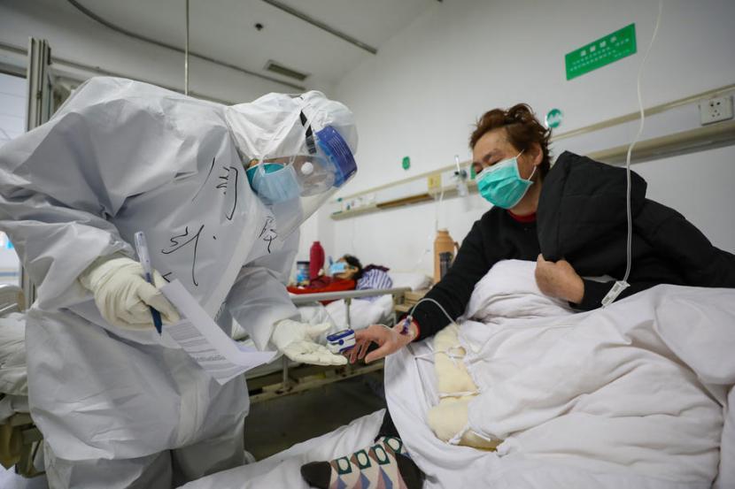 Dokter menggunakan pulse oxymeter untuk memeriksa saturasi oksigen pasien Covid-19  di Wuhan, Provinsi Hubei, China, 13 Februari 2020.