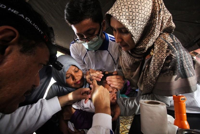Dokter spesialis Telinga, Hidung dan Tenggorokan (THT) memeriksa telinga anak saat program kesehatan telinga Millenial Road Safety Festival Polres Lhokseumawe, di Lhokseumawe, Aceh, Ahad (10/3/2019).
