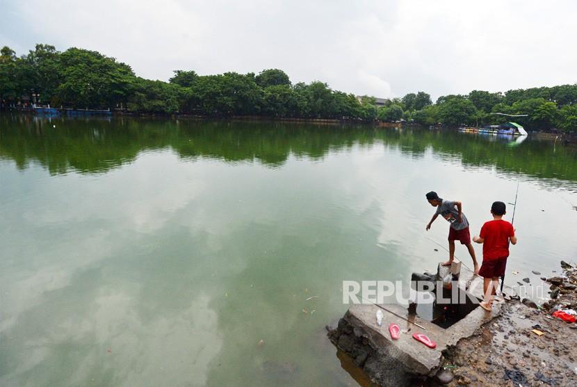 Dua anak memancing di Danau Sunter, Jakarta, Kamis (18/1).