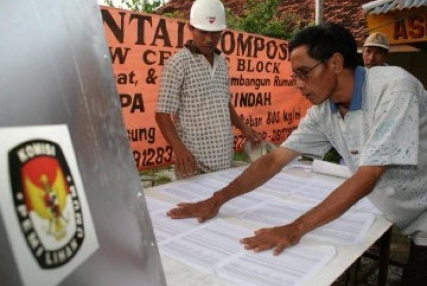 Dua anggota KPPS menyiapkan Tempat Pemungutan Suara (TPS).