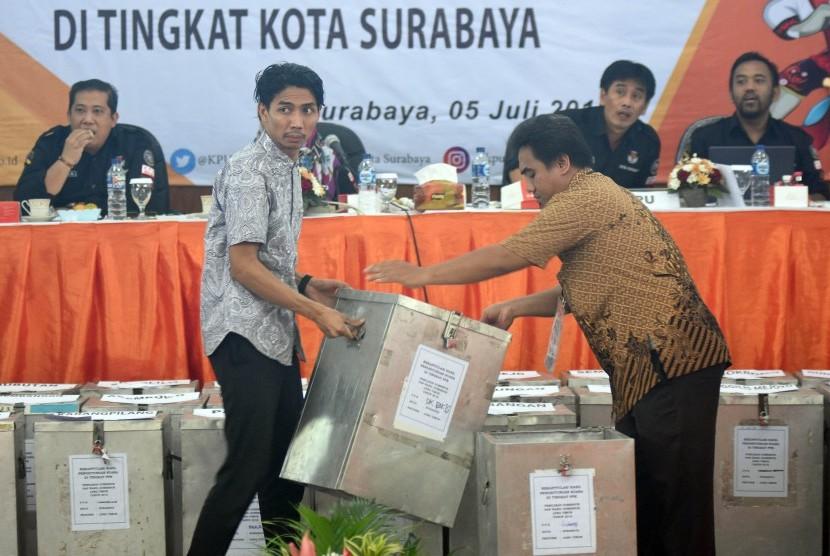 Dua anggota Panitia Pemilihan Kecamatan (PPK) mengangkat kotak suara ketika Rapat Pleno Rekapitulasi Penghitungan Suara Pilgub Jatim 2018 di Kantor Komisi Pemilihan Umum (KPU) Surabaya, Jawa Timur, Kamis (5/7).