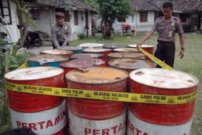 Dua anggota polisi menyegel drum-drum berisi BMM ilegal (ilustrasi).