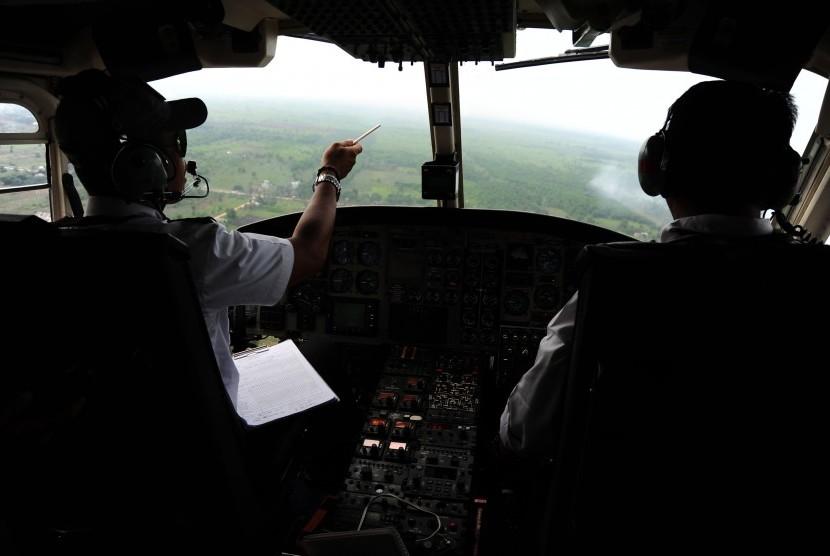 Dua awak pesawat Heli Bell 412 Kementerian Lingkungan Hidup dan Kehutanan memantau kebakaran hutan dan lahan (karhutla) di Kabupaten Kubu Raya, Kalbar, Kamis (25/8).