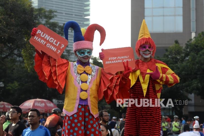 Dua badut berpose saat mensosialisasikan tolak Pungutan Liar (Pungli) di Jakarta, Ahad (17/9).