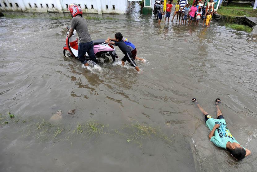 Dua bocah membantu mendorong motor yang mogok ketika melintasi banjir di Syech Yusuf Sungguminasa, Gowa, Sulsel, Selasa (24/12).